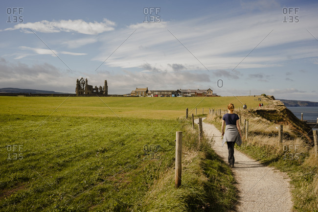 Woman walking along path between whitby and robinshood bay with