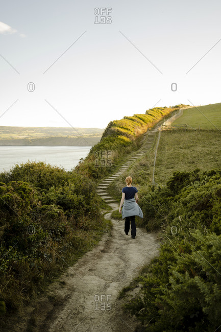 Red headed woman walking along path between whitby and robinshoo