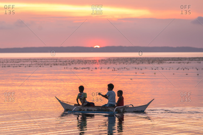 Philippines - may 7, 2018: kids in a boat during sunset