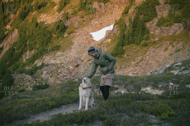 Man petting dog in the mountains at sunset