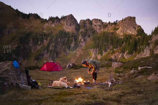 Camping in the alpine backcountry with campfire tent and dog