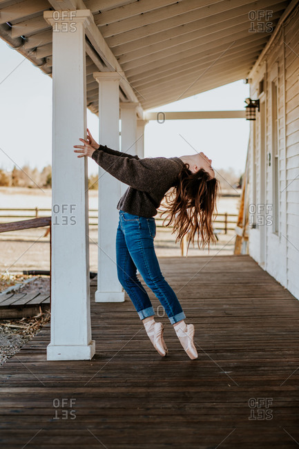 Vertical portrait of teen ballerina dancing on patio