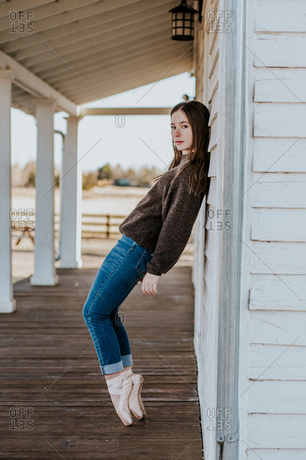 Vertical portrait of teen girl leaning against wall in pointe shoes