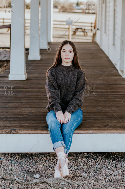 Teen girl sitting on the end of a porch with ballet shoes on