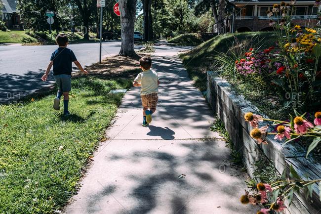 Two young boys running on a sidewalk in neighborhood