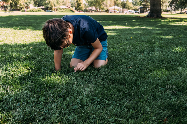 Young boy playing in the grass at a park on a warm day