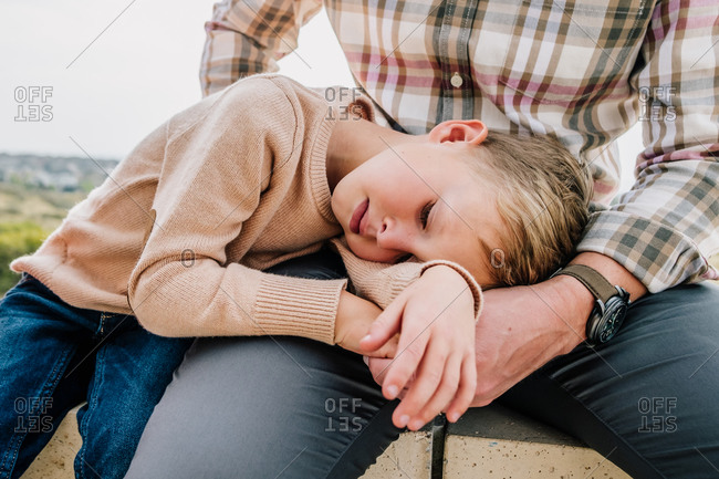 Young boy cuddling father outside
