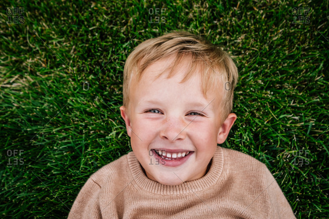 Happy young boy laying in grass smiling