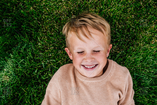 Smiling young boy laying in grass outside