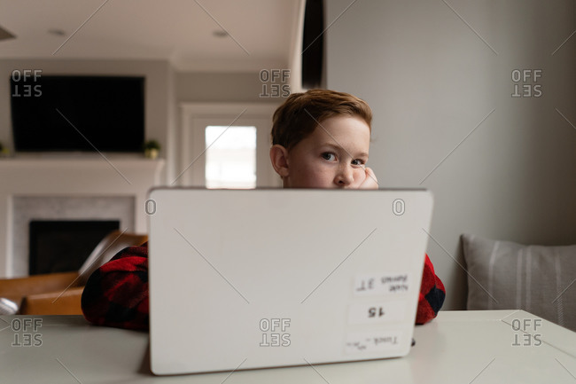 Young redhead boy looking bored over laptop computer indoors at table