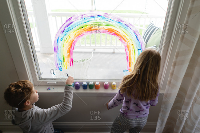 Top down view of siblings painting rainbow on living room window