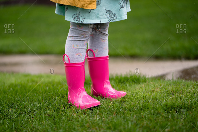 Legs view of little girl in bright pink rain boots in yard