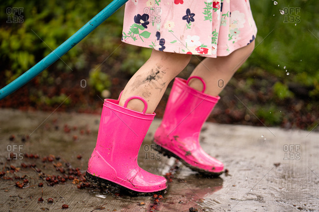 Side view of bottom half of girl playing with hose muddy legs