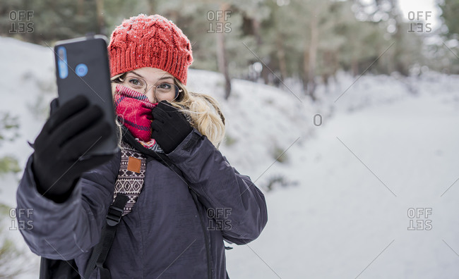 Smiling girl enjoying winter and taking selfie while snowing