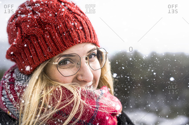 Smiling woman wearing wool bonnet and scarf in a winter cold day. happy girl in a sweater outdoor in snow.
