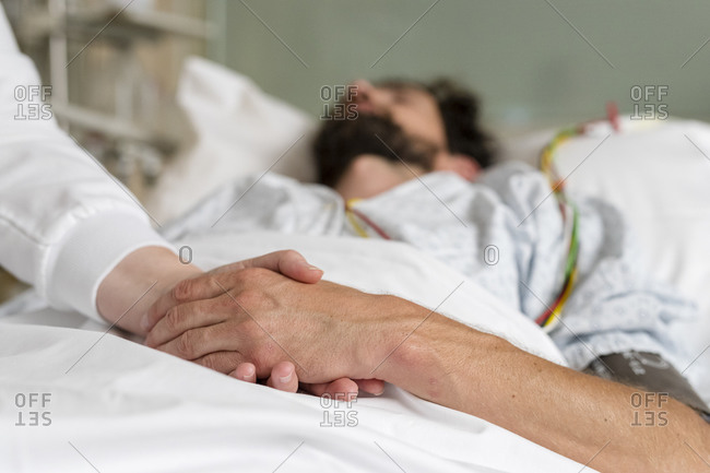 Healthcare staff caring for a patient in hospital bed