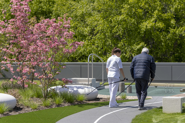 A caregiver walks with a patient in a garden