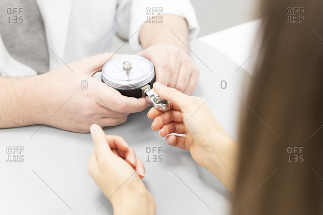 An orthopedist assesses the strength of the fingers of one hand