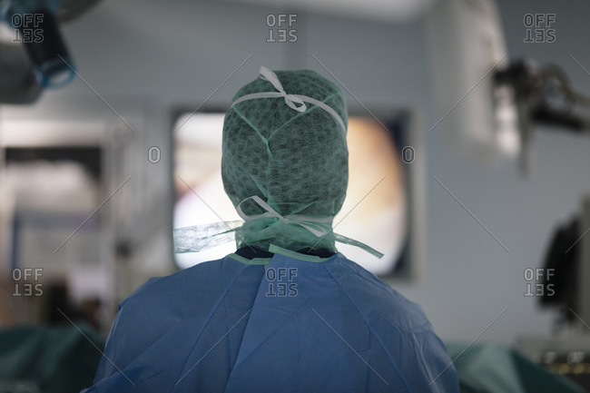 A surgeon looks at a monitor screen during surgery