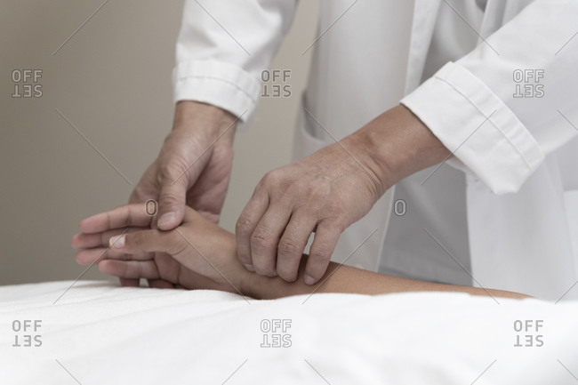A doctor takes a patient's pulse on the wrist
