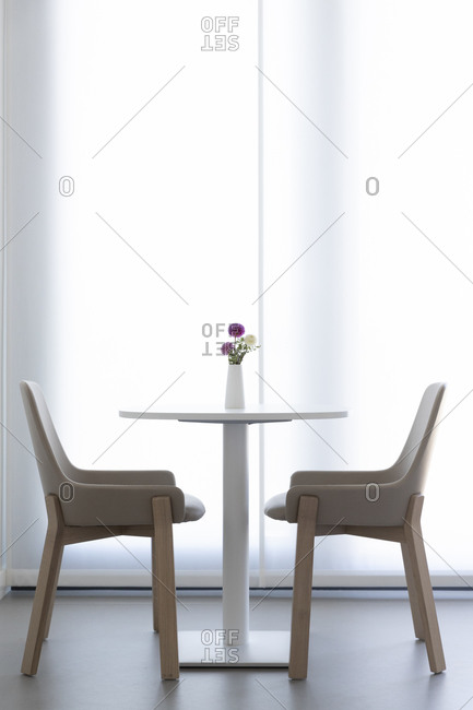 A round table with a vase and two wooden chairs