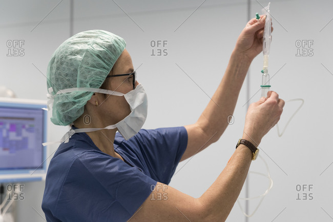 An anesthetist prepares an infusion in the operating room