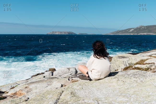 Young woman with curly hair sitting on the rocks looking at sea