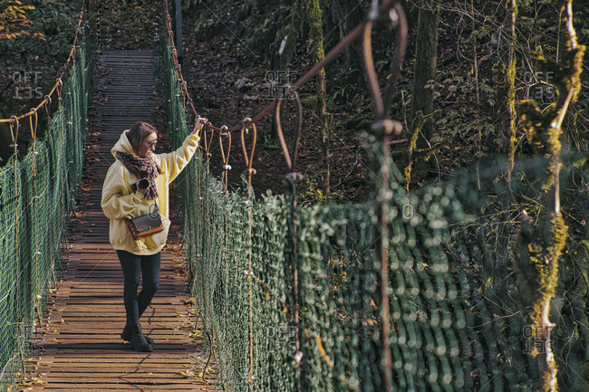 Young woman crossing  suspension bridge