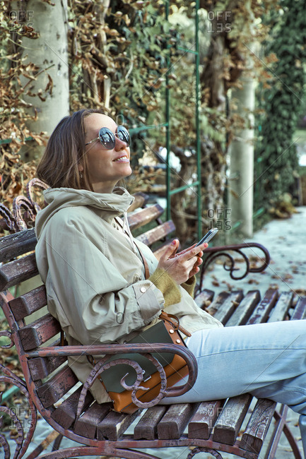 Relaxed young woman sitting on a bench using cell phone