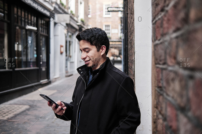 Latino young man standing on the street checking his phone with a friendly expression