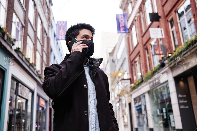 Young Hispanic man wearing a face mask talking on the phone on the street