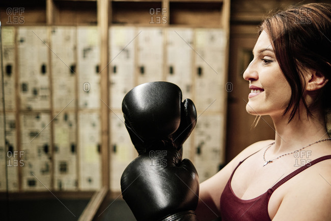 Young female boxer smiling while training at the gym