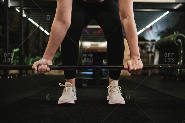 Close-up of a woman doing deadlift exercise alone at the gym