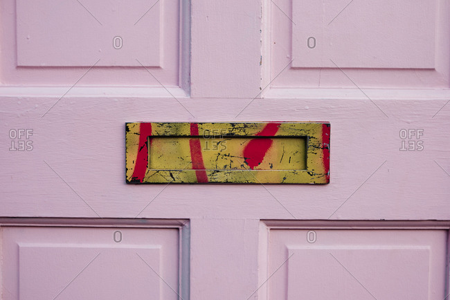 Detail of a pink door with an old yellow-colored mailbox or letterbox sprayed with red