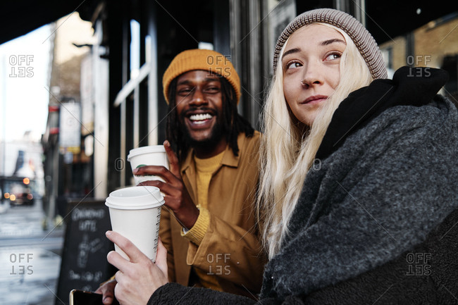 Multiracial couple sitting outdoors laughing while drinking coffee. biracial lovers on a date concept.
