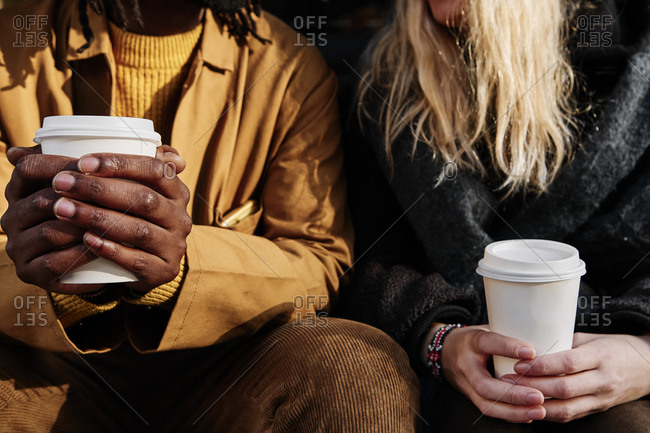 Multicultural unrecognizable friends holding a paper cup of coffee while sitting together. focus on the hands.