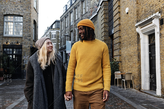 Biracial couple holding hands as they walk on the street staring at each other with affection. multicultural couple on a date concept.