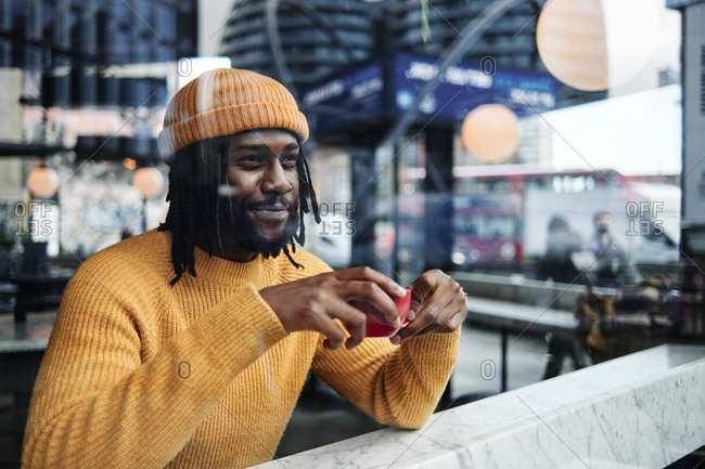 Young African guy looking through a window as he drinks a cup of coffee at a cafe, reflection of the city on the glass