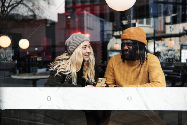 Young biracial couple talking at the window of a cafe, reflection of the city on the glass