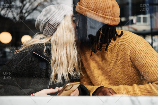 Happy biracial couple kissing at the window of a cafe, reflection on the glass