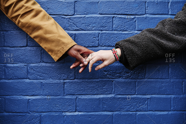 Interracial couple holding hands, blue wall background. love symbolic concept.