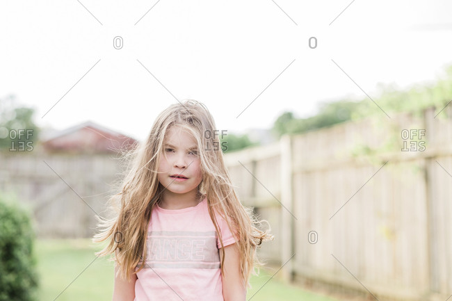 Young girl with long blonde hair standing in back yard