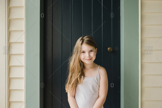 Smiling young girl standing outside in front of a door