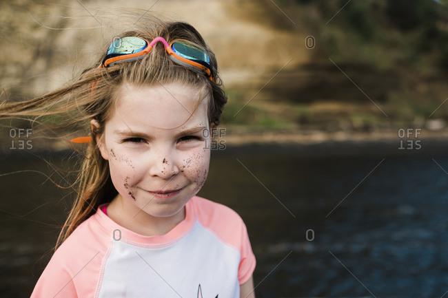 Smiling girl on waters edge wearing Rashia and googles