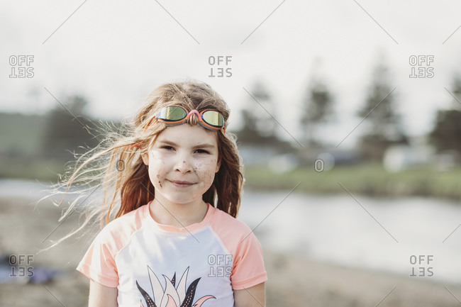 Young girl wearing googles and rash guard at the beach