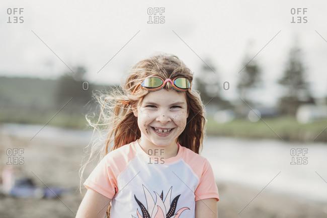 Laughing girl wearing Rashia and googles at the beach