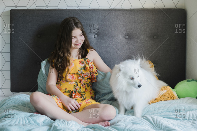 Young girl sitting on a bed patting a cute small fluffy white dog