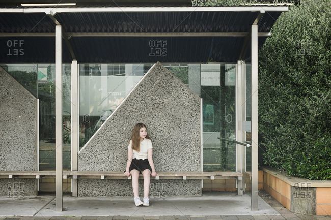 Young girl sitting alone on a wooden seat at an empty bus stop