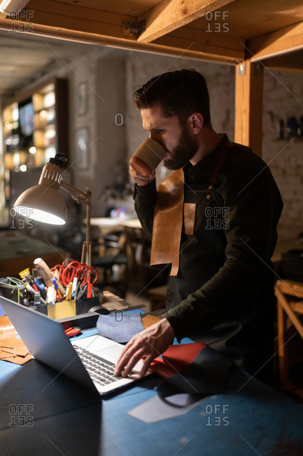Craftsman drinking hot beverage and using laptop