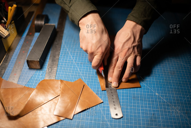Cropped artisan cutting leather on table